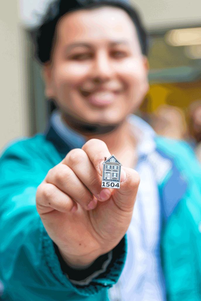 Student holding a La Casita Institute pin